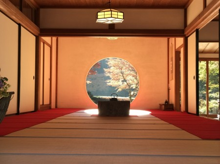 Circular window in the main hall(Hojo) with autumn leaves at Meigetsuin in Kamakura
